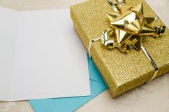 Un présent enveloppé en or avec une carte photographie stock