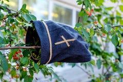 Un prêtre chrétien de coiffe simple de tissu accrochant sur une branche d'arbre image libre de droits