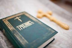 Un prêtre tient une croix photographie stock