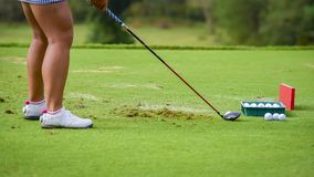 Un pratice del golfista para empujar la pelota de golf para agujerear fotos de archivo libres de regalías