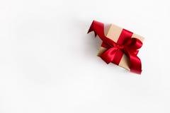 Un presente con una cinta roja en fondo blanco de madera foto de archivo