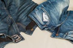un preservativo e un paio dei jeans sullo strato Fotografie Stock