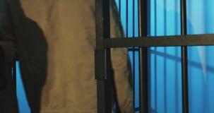 Un preso batido con una barba detrás de una rejilla de la prisión almacen de video