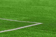 Un primer de un césped verde artificial del fútbol con una esquina mA fotografía de archivo
