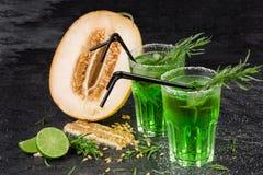 Un primer de frutas exóticas Cócteles verdes del alcohol con la paja Corte el melón Anillos en D del estragón y cal fresca en un  Fotografía de archivo