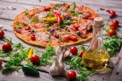 Un primer de la pizza caliente del margarita en un fondo rústico de la tabla Pizza italiana entera con las verduras y el aceite d Foto de archivo libre de regalías