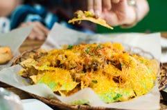 Un primer de la placa por completo de nachos foto de archivo