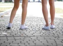Un primer de las piernas del ` de los teenages en las zapatillas de deporte blancas que se colocan en un fondo cobbled borroso Co imagen de archivo