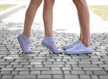 Un primer de las piernas del ` de los teenages en las zapatillas de deporte blancas que se colocan en un fondo natural borroso Co Fotos de archivo libres de regalías