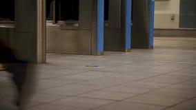 Un primer de los pies de los viajeros que caminan a través de una puerta de la entrada en una línea estación de Canadá en Vancouv metrajes