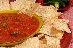 Un primer de un tazón de fuente de salsa con las virutas de tortilla y el PE del jalapeno Foto de archivo libre de regalías