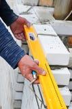 Un primer de un trabajador del albañil que instala bloques del wite y que calafatea la albañilería del ladrillo articula la pared Imagenes de archivo