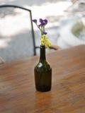 Un primer de una botella de vino de cristal con las flores frescas coloridas en un fondo borroso Un florero con las flores en un  Imagenes de archivo