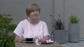 Un primer de una mujer envejecida bonita que se sienta en la terraza Ella es sola, bebe té, refleja almacen de metraje de vídeo