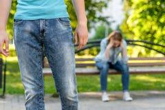 Un primer del hombre joven sale de una muchacha En fondo, la muchacha en el banco está gritadora y triste El concepto del problem Foto de archivo libre de regalías