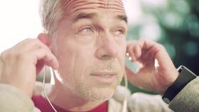 Un primer del retrato de un hombre maduro activo con los auriculares que se colocan al aire libre en ciudad almacen de metraje de vídeo