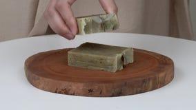 Un primer del ` s de la mujer da poner barras del jabón natural de la lavanda en una bandeja de madera redonda En el top ella pon