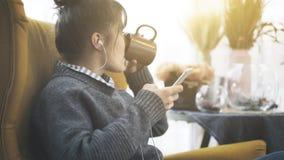 Un primer una muchacha en los auriculares que sostienen un teléfono que se sienta en un té de consumición de la silla grande Fotografía de archivo