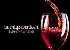 Un primo piano dei desideri di 2017 buoni anni con il vetro del vino rosso Fotografia Stock Libera da Diritti