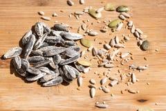 Un primo piano dei semi del girasole, del sesamo e di zucca sopra una tavola di legno fotografia stock