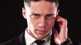 Un primo piano del fronte di un tipo che con un fronte serio ascolta il suo ricevitore telefonico speciale stock footage