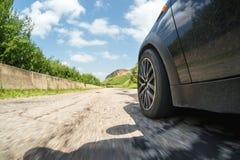 Un primo piano del lato dell'automobile e di una ruota di filatura che guida lungo l'asfalto all'alta velocità Fotografia Stock Libera da Diritti