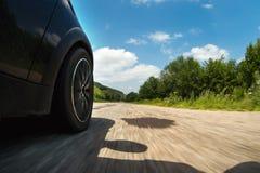 Un primo piano del lato dell'automobile e di una ruota di filatura che guida lungo l'asfalto all'alta velocità Fotografia Stock