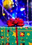 Un primo piano del regalo di un nuovo anno in un contenitore di regalo con un arco e di un fondo vago molle di un albero di Natal fotografia stock