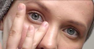 Un primo piano del ` s della donna di 30 ` s osserva esaminando la macchina fotografica ed ha messo una crema dell'occhio archivi video