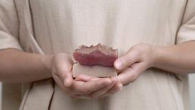 Un primo piano del ` s della donna passa la tenuta della barra di sapone rosa fatto a mano archivi video