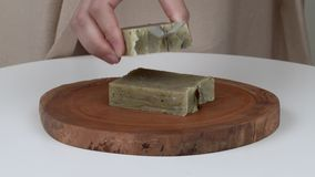 Un primo piano del ` s della donna passa mettere le barre del sapone naturale della lavanda su un vassoio di legno rotondo Sulla