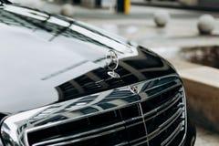 Un primo piano del segno di Mercedes e la parte anteriore di nuova automobile nera di lusso di Mercedes-Benz fotografie stock libere da diritti