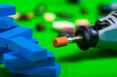 Un primo piano del trapano grigio con i piccoli pezzi di legno blu su un fondo verde Fotografia Stock Libera da Diritti