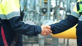Un primo piano dell'uniforme d'uso del lavoratore maschio due che fa stretta di mano alla fabbrica dell'industria pesante stock footage