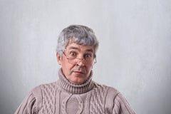 Un primo piano dell'uomo anziano sorpreso con capelli grigi e le grinze che indossano gli occhiali che guardano con gli occhi spa Fotografie Stock