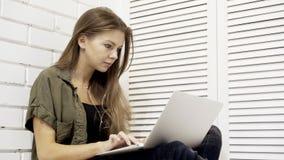 Un primo piano della studentessa concentrata giovani sta funzionando con il computer portatile che si siede sul pavimento Immagini Stock