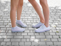 Un primo piano delle gambe del ` di teenages in scarpe da tennis bianche che parlano l'un l'altro su un fondo cobbled vago Copi l immagine stock libera da diritti
