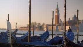 Un primo piano delle gondole coperte che ondeggiano su un pilastro contro la vista vaga di Venezia stock footage