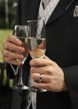 Le mani degli uomini con i vetri del champagne Immagini Stock
