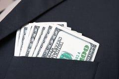 Un primo piano di cento banconote in dollari in tasca del vestito Fotografie Stock