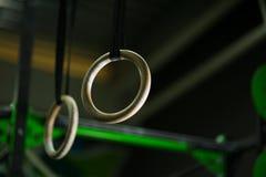Un primo piano di due ancora anelli di legno, anelli costanti che appendono liberamente, di sostegno tramite una cinghia su un bu Immagine Stock