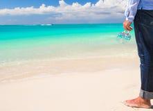 Un primo piano di due bicchieri di vino in mano di un uomo sulla spiaggia sabbiosa bianca Immagini Stock