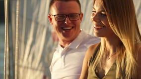 Un primo piano di due che sorridono e amanti di risata nel tempo di sera su una barca a vela in mare stock footage