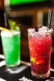 Un primo piano di due cocktail rossi e verdi variopinti con calce e zucchero bruno nella barra, fondo vago fotografia stock