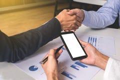 Un primo piano di due genti di affari che stringono le mani mentre sedendosi alla t immagini stock