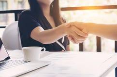 Un primo piano di due genti di affari delle donne che stringono le mani al posto di lavoro Immagine Stock Libera da Diritti