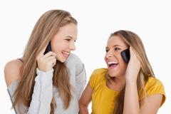 Un primo piano di due giovani donne che ridono sul telefono Immagine Stock Libera da Diritti