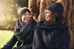 Un primo piano di due giovani donne sorridenti che si appoggiano il tronco di albero in parco autunnale Immagini Stock