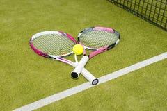 Un primo piano di due racchette di tennis con una pallina da tennis Fotografia Stock