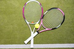 Un primo piano di due racchette di tennis rosa con una pallina da tennis Fotografia Stock